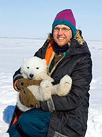 Nick Lunn, polar bear researcher for Environment Canada, uses the cub of a drugged female for a photo op